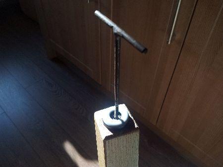 Fotografie s jednou nohou od židle kde pomocí vrtáku připravuji ručně díru pro navrtání šroubku pro ochrannou podložku | Ochranné podložky