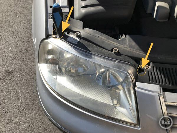 Fotografie, kde jsou zvýrazněná místa, kam je nutné vložit šroubovák a vyndat spodní šrouby předního světlometu