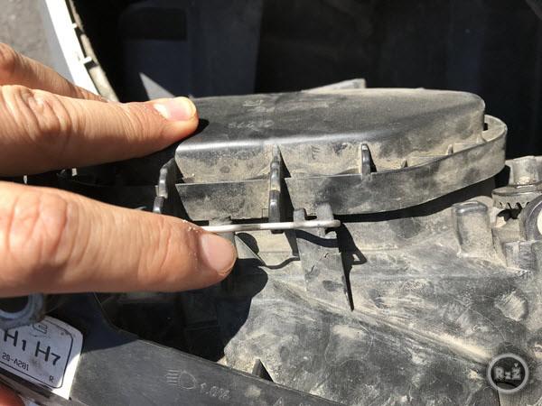 Fotografie předního světlometu a zaklapnutí upínacího drátu ochranného pouzdra světla zevnitř - Výměna žárovky předních světel   Volkswagen Sharan   Auto   Udělej si sám