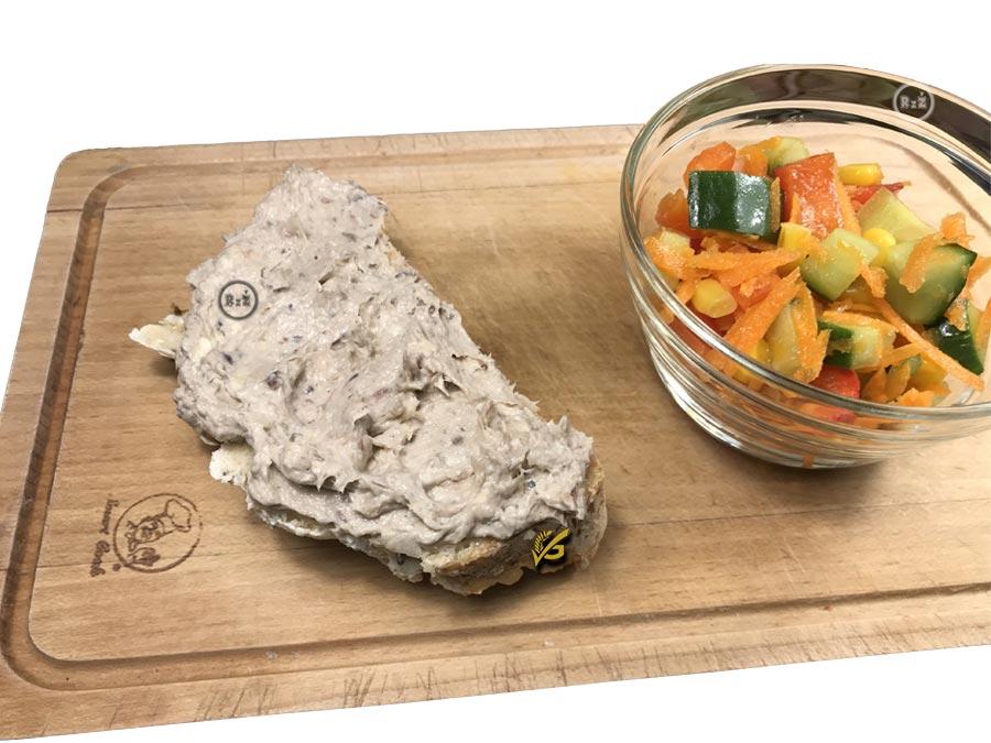 Bezlepková domácí rybičková pomazánka namazaná na bezlepkovém chlebu ležícím na dřevěném prkénku vedle misky naplněné čerstvým zeleninovým salátem v pozadí bílá barva | Bezlepková rybičková pomazánka | Bezlepkové recepty | Rady ze života