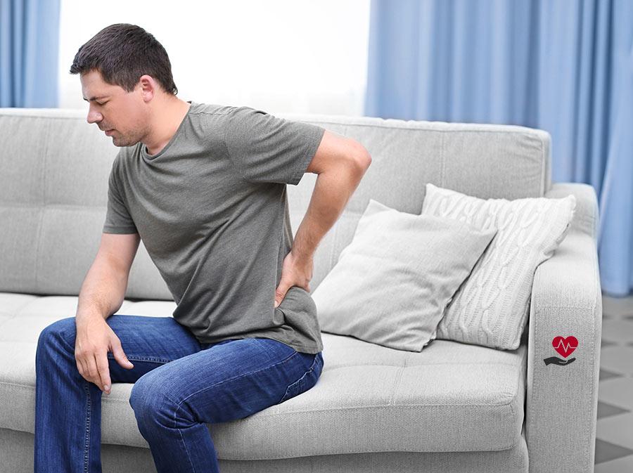 Muž sedící na světlém gauči těžce sedící a rukou držící svá bolavá záda v oblasti páteře nad pasem v pozadí se světle modrými záclonami a světlem procházejícím přes bílou záclonu (na gauči menší symbol zdraví v podobě dlaně nad kterou je zobrazeno srdce se srdečním tepem)