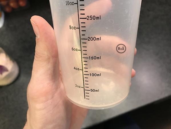 Fotografie - sůl v odměrce - příprava roztoku pro inhalaci (mořská sůl a voda)