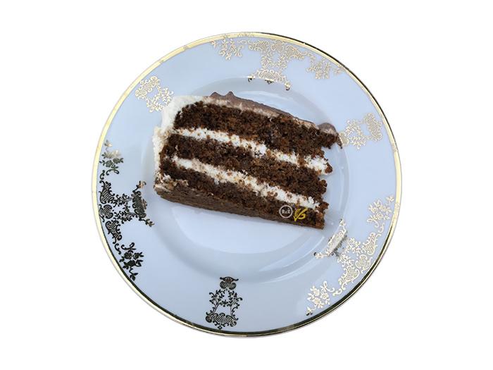 Fotografie bezlepkového mrkvového dortu na bílém talíři se zlatými ozdobnými obrazci na bílém pozadí | Bezlepkový mrkvový dort