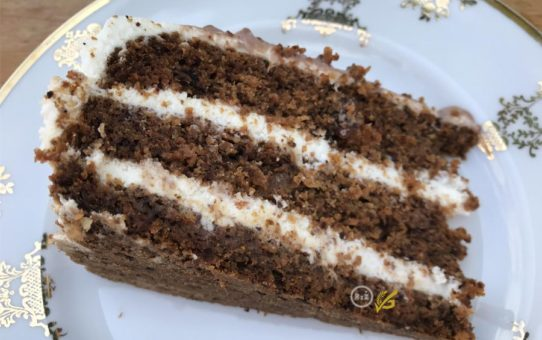 Fotografie bezlepkového mrkvového dortu na bílém talíři se zlatými ozdobnými obrazci na bílém pozadí   Bezlepkový mrkvový dort