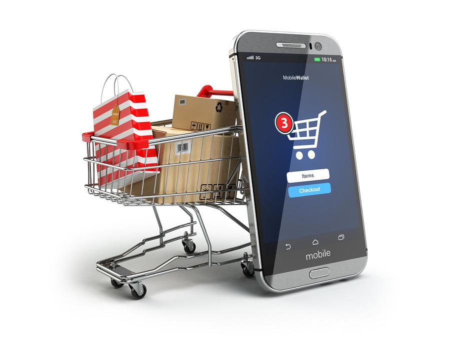 Plný nákupní košík taškami nákupu s opřeným mobilním zařízením sloužícím k on-line nákupům