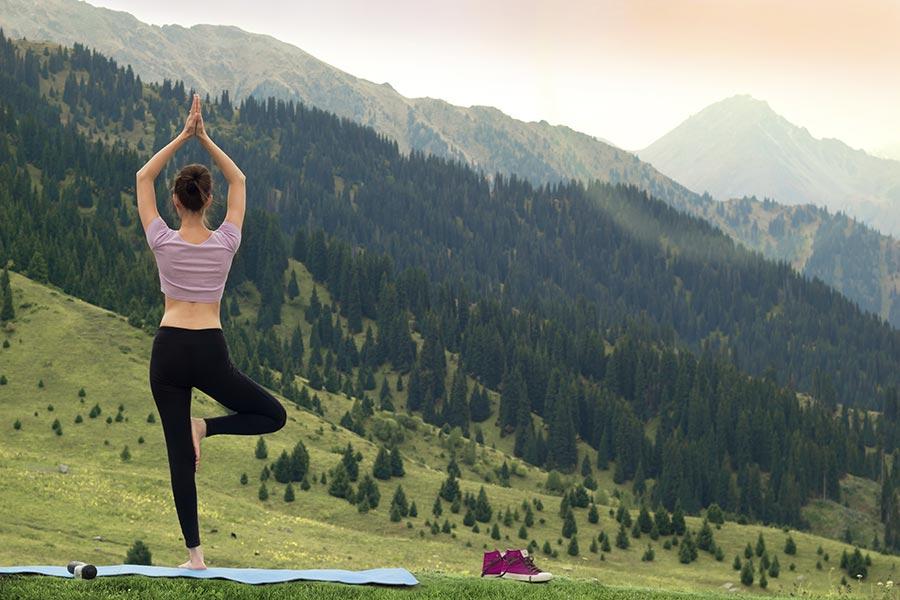 Fotografie ženy stojící na podložce v přírodě v pozadí hory - žena se snaží o rovnováhu - balancuje | zdroj: shutterstock