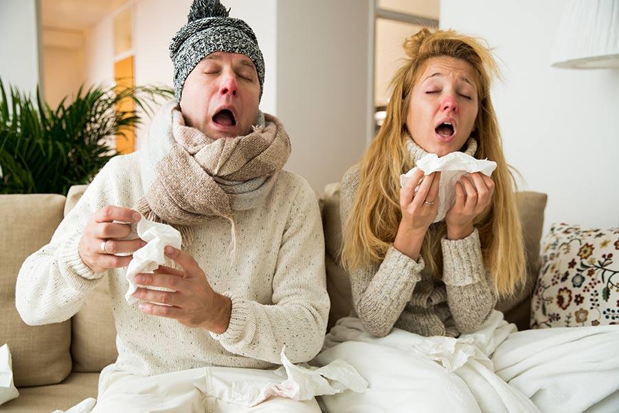 Ilustrativní foto pro článek Zadní rýma - příčina respiračních onemocnění | Žena a muž sedící doma nachlazení - v rukou drží bílé kapesníky majíc červené nosy - mají rýmu a nevypadají vůbec dobře (Zdroj: shutterstock.com)