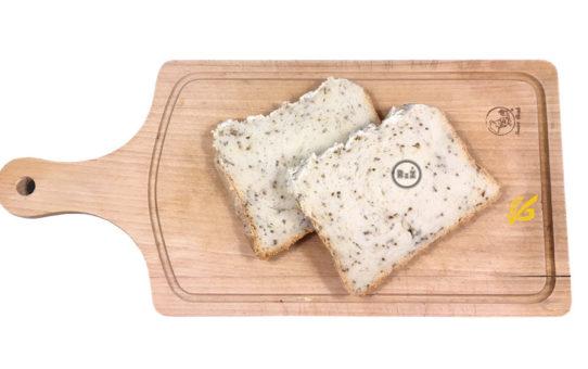 Fotografie bezlepkový chléb z domácí pekárny - nakrájené dva plátky ležící na dřevěném prkénku | Bezlepkový chléb z domácí pekárny | Bezlepkové recepty