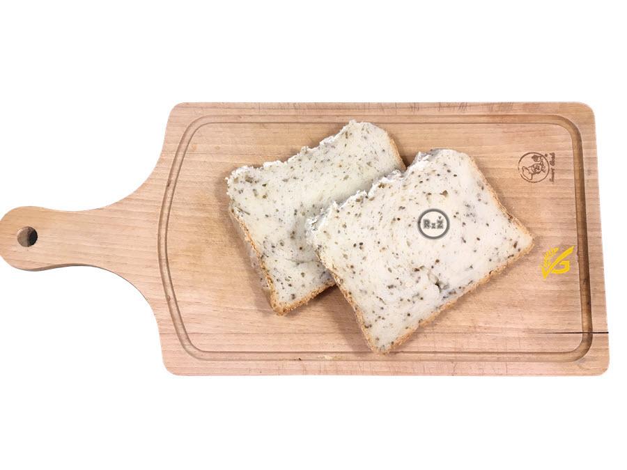 Fotografie bezlepkový chléb z domácí pekárny - nakrájené dva plátky ležící na dřevěném prkénku   Bezlepkový chléb z domácí pekárny   Bezlepkové recepty