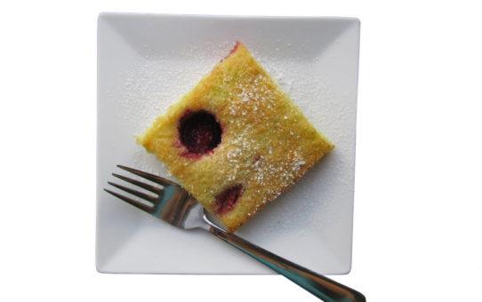 Fotografie bezlepkového táče (buchty) na bílém talíři na bílém pozadí   Bezlepkový táč s ovocem